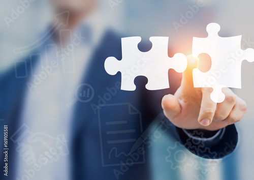 Mergers and acquisition concept with consultant touching puzzle pieces icons Canvas Print