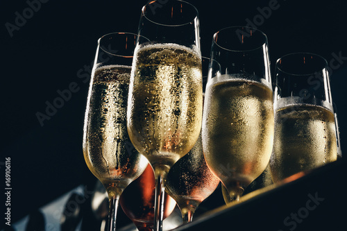a row of glasses filled with champagne are lined up ready to be served Fototapeta