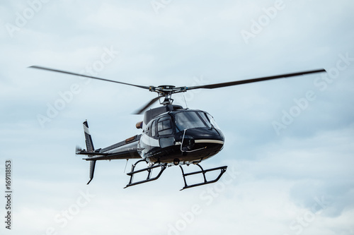 Tuinposter Helicopter Black tourist helicopter flying