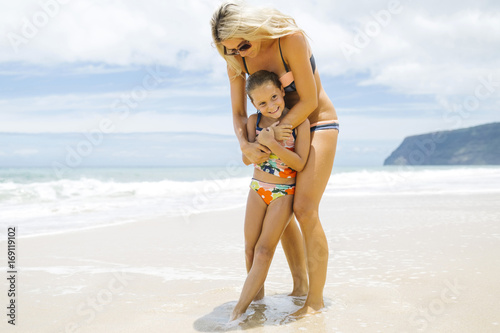 Mother embracing daughter on the beach - 169119102