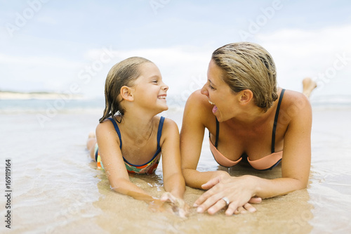 Staande foto Strand Mother lying with daughter (6-7) on beach