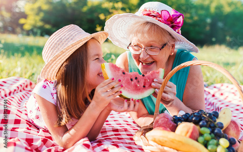 Little girl and her grandmother enjoying in picnic together. Nature, lifestyle