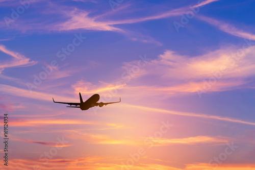 Zdjęcie XXL Sylwetka pasażerski samolot lata daleko w niebo dużej wysokości nad słońce podczas zmierzchu