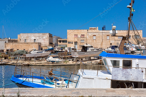 Poster Channel Mazara del Vallo (Italy) - Day view of canal, fishing boats and downtown