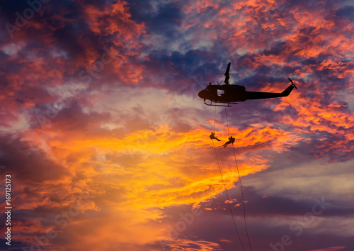 Fotografía  silhouette soldiers in action rappelling climb down from helicopter with mili