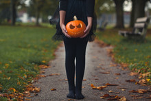 Girl In A Black Tutu And Tights Holding A Carved Pupkin