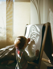 Small Boy Drawing On Paper On An Easel