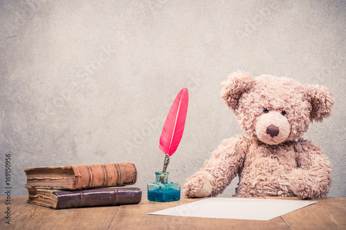 Retro Teddy Bear toy sitting at the old wooden desk with paper sheet, red quill pen in the inkwell and old books front concrete wall background. Vintage style filtered photo