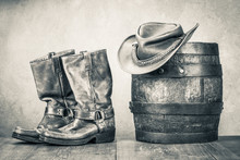 Wild West Old Retro Leather Cowboy Boots, Hat And Oak Barrel. Vintage Style Sepia Photo