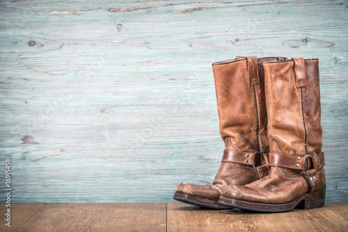 Wild West old retro leather cowboy boots front textured wooden wall background Tapéta, Fotótapéta