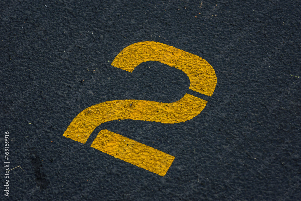 Fototapeta stenciled number 2 two in yellow paint on blacktop in parking lot - for use as background