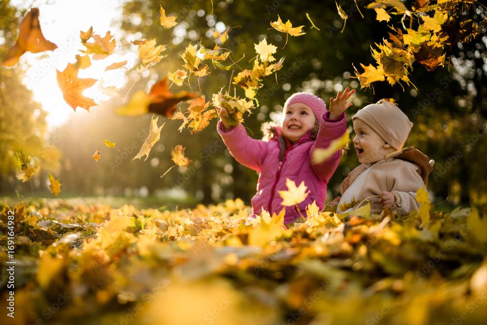 Fototapety, obrazy: Kids having fun in park, throwing up leaves.
