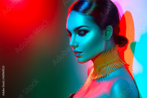 Foto op Plexiglas Beauty Fashion model woman in colorful bright lights posing. Portrait of beautiful sexy girl with trendy makeup