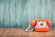Old Orange Retro Rotary Telephone On Table Front Grunge Textured Wooden Wall Background. Vintage Instagram Style Filtered Photo