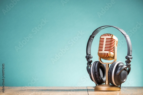 Photo Retro golden microphone and headphones on table front gradient aquamarine background