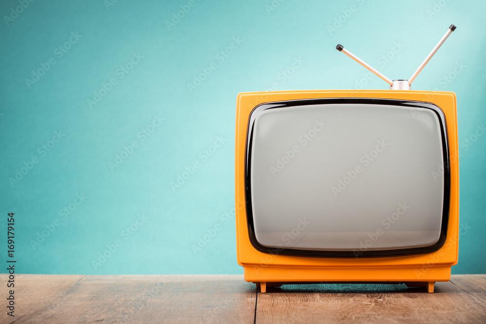 Fototapeta Retro old orange TV receiver on table front gradient aquamarine wall background. Vintage style filtered photo
