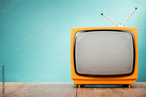 Poster Retro Retro old orange TV receiver on table front gradient aquamarine wall background. Vintage style filtered photo