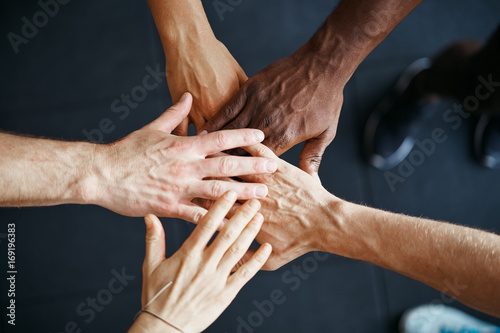Fotografía  Diverse people standing with their hands together in a gym