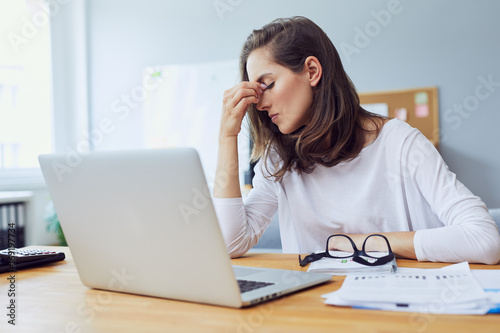 Valokuvatapetti Beautiful stressed young office worker sitting at desk holding head because of p
