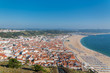 Nazare beach in Portugal in summer, people in holidays and tiles roofs of the village