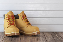 Yellow Boots On A Wooden Table