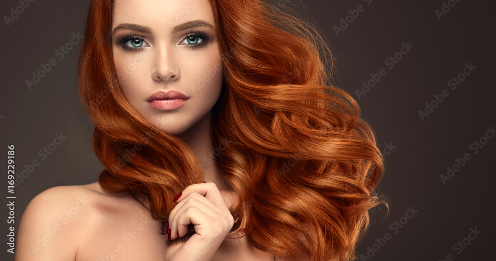 Fototapeta Beautiful model girl with long red curly hair .Red head . Care products ,hair colouring .