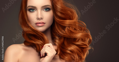 Beautiful model girl with long red curly hair .Red head . Care products ,hair colouring .