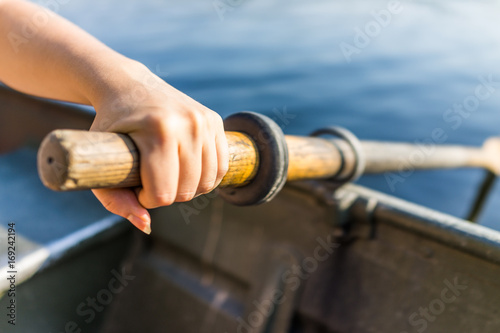 Photo Female hand on row boat oar closeup in summer with water