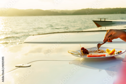 Photo Hand with fork eating food on the deck of a yacht