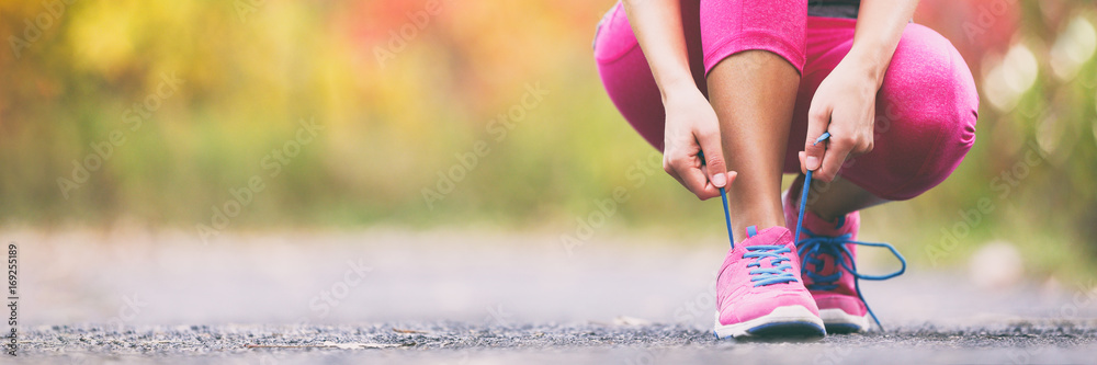 Fototapeta Running shoes runner woman tying laces for autumn run in forest park panoramic banner copy space. Jogging girl exercise motivation heatlh and fitness.