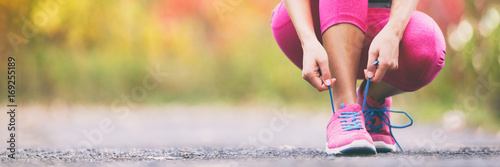 Poster Jogging Running shoes runner woman tying laces for autumn run in forest park panoramic banner copy space. Jogging girl exercise motivation heatlh and fitness.