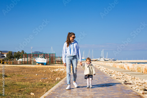 Poster Jogging Mother and little daughter walking on the beach.