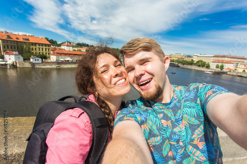 Photo Happy romantic couple of tourists makes selfie self-portrait in Prague while traveling across Europe