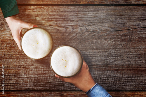 Fotografía Couple of Man and Woman holding a Glass of Beer to Celebrate in Restaurant or Ba