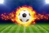 Fototapeta Sport - Burning soccer ball above green football stadium