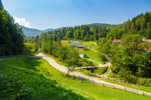 Ukrainian Coutryside Settlement In Carpathian Mountains With Bridge Over The Creek
