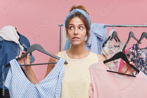 Foto Cute female purchaser standing in fitting room, holding two stylish dresses, hav