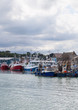 Fishing trawlers berthed at the quay on a cloudy day.