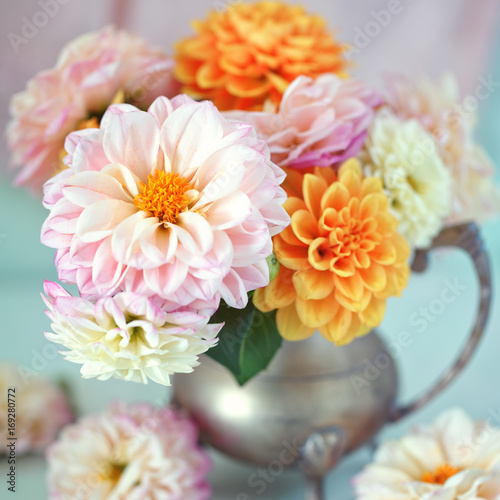 Foto Beautiful bouquet of a yellow and pink dahlias on a light green background