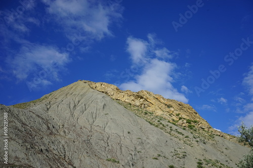 the hill of volcanic origin on the background of blue sky with white clouds in the Crimea
