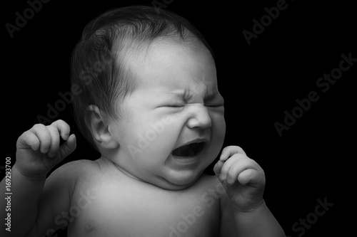 Photo  newborn baby crying. Baby's portrait in low key