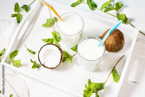 Fototapeta Coconut vegan milk coctail in glass on wooden background