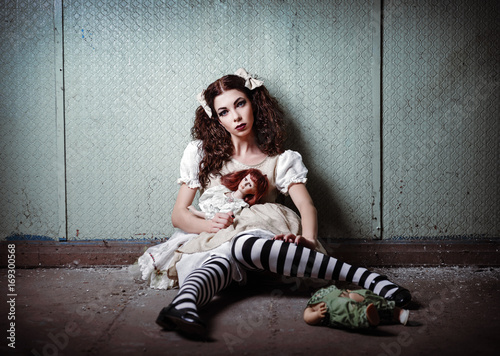 Portrait of strange lonely girl with dolls in abandoned place Wallpaper Mural