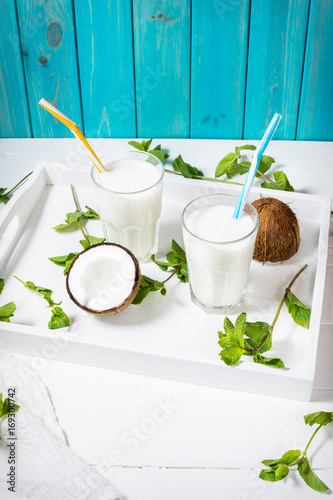 Obraz na plátně Coconut vegan milk coctail in glass on wooden background