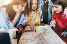 Three Girlfriends Planning Their Vacation Sitting At Table Around Map Choosing The Destination