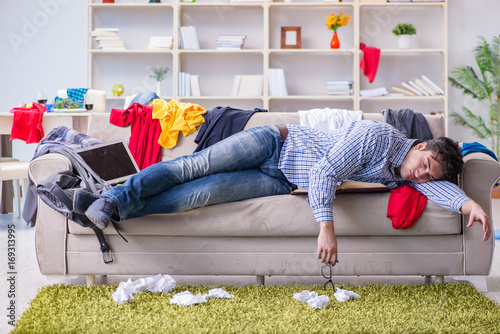 Obraz Young man working studying in messy room - fototapety do salonu