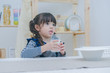 A little cute girl drinking milk after have a breakfast in the dinning room, healthy food