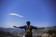 Man standing on a mountain peak with wide spread hands