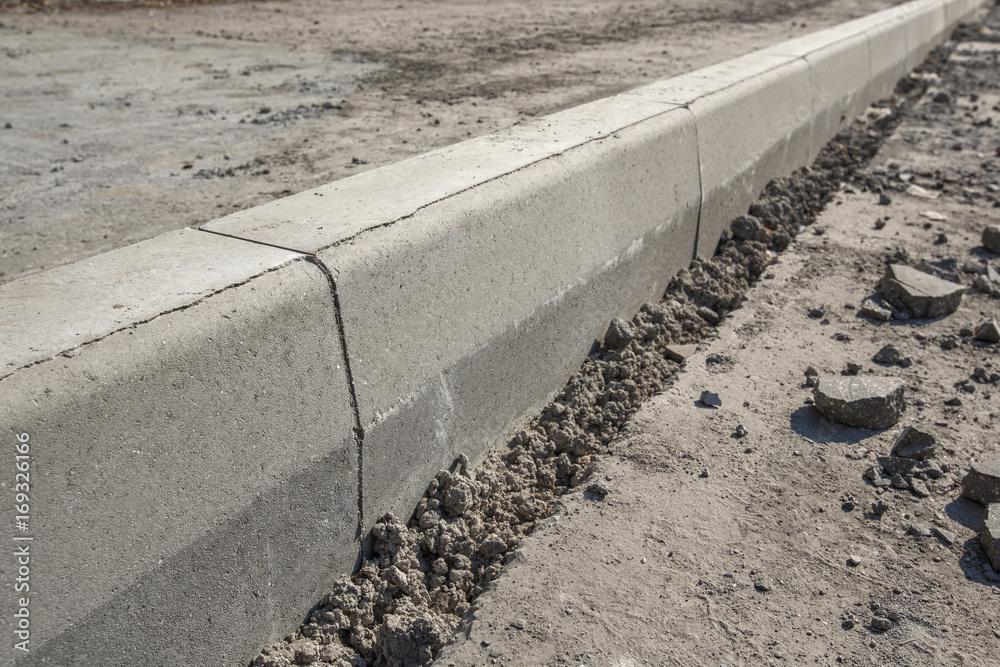 Fototapeta Sidewalk under construction, concrete curb  installation in progress.