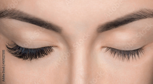 Eyelash removal procedure close up. Beautiful Woman with long lashes in a beauty salon. Eyelash extension.